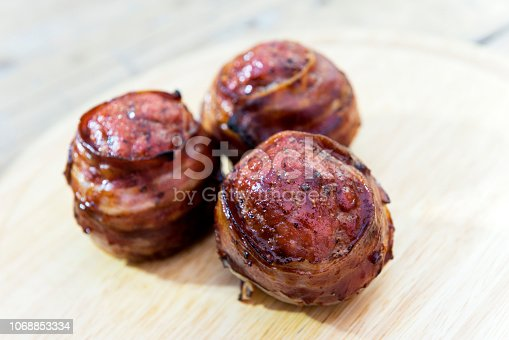 istock Three meatballs and covered with bacon on cutting board 1068853334