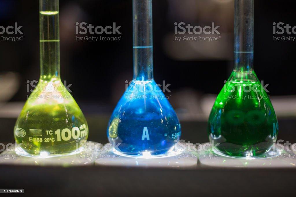 Three medical flasks bottles yellow blue gren liquid stock photo