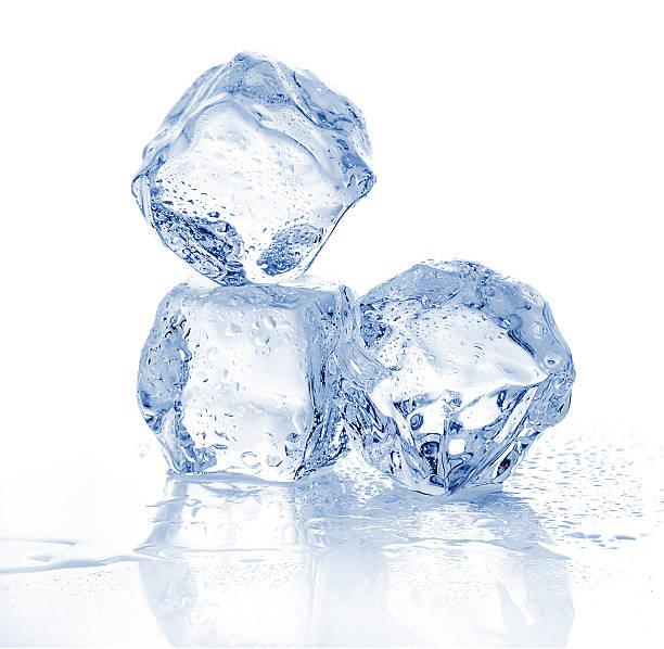 Three melting ice cubes on white background. stock photo