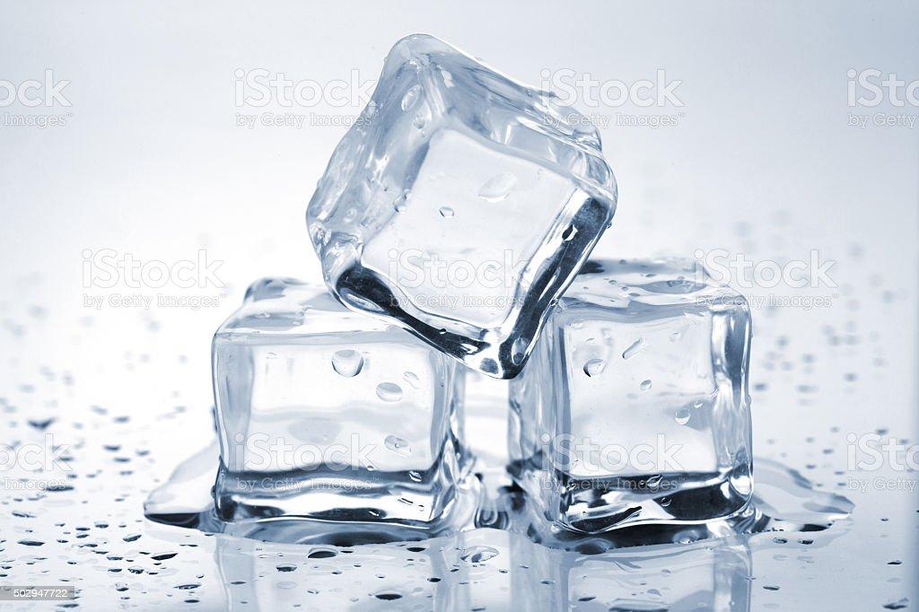 Three melting ice cubes stock photo