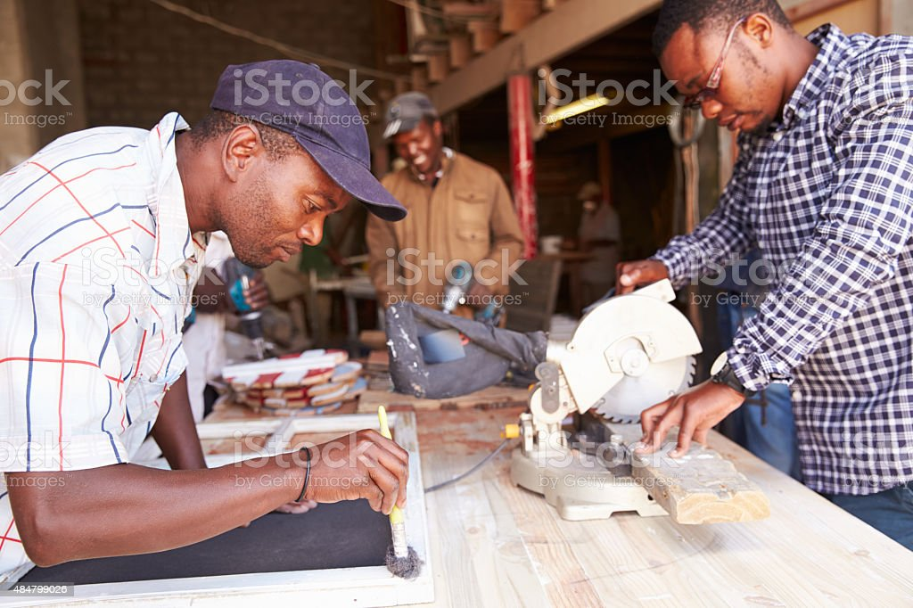 Three men at work in a carpentry workshop, South Africa
