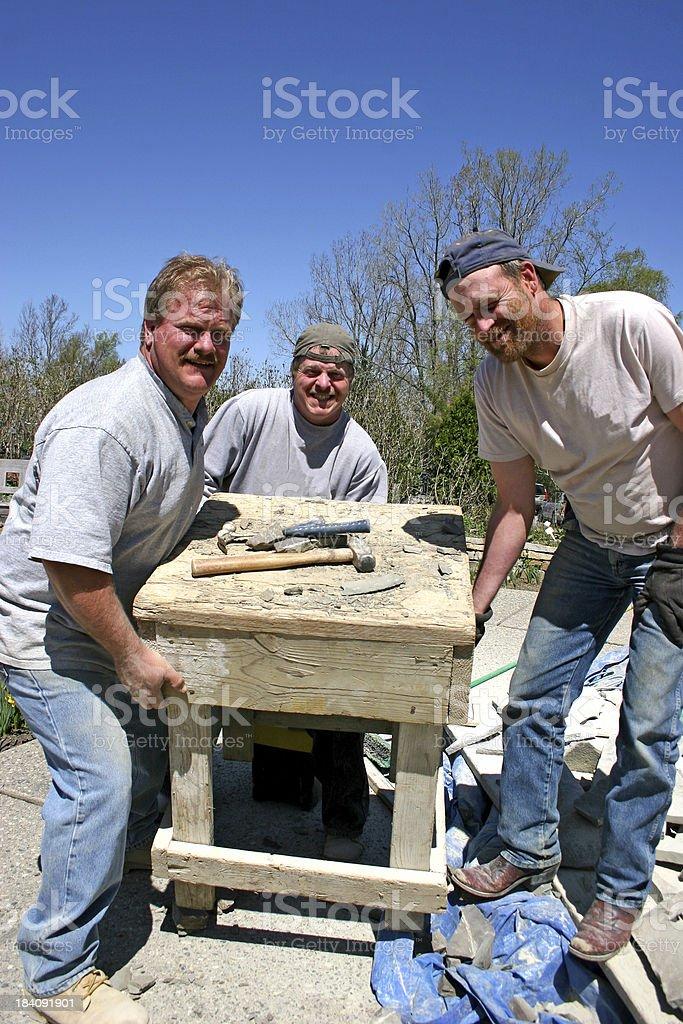Three Men Heavy Lifting Vertical royalty-free stock photo