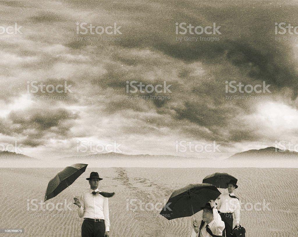 Three Men Holding Umbrella on Sand royalty-free stock photo