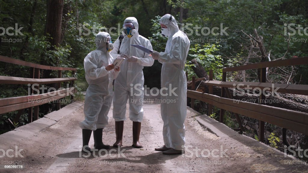 Three men in biohazard suits standing on a bridge stock photo