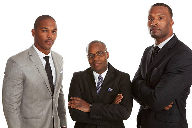 Three men in suits looking confident on white background stock photo