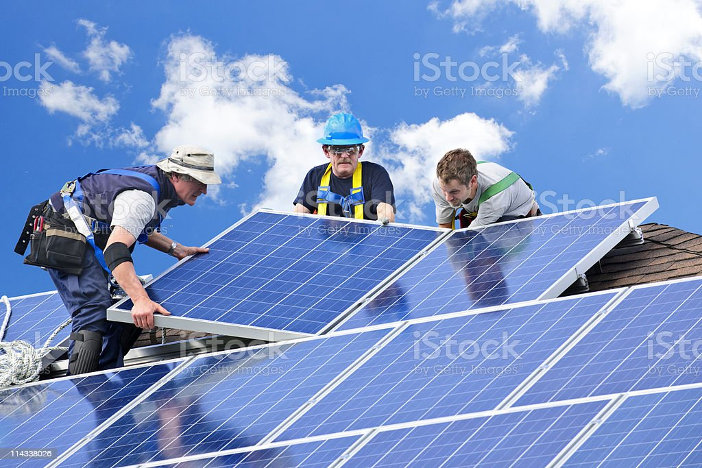 Three men installing solar panels on a house roof stock photo