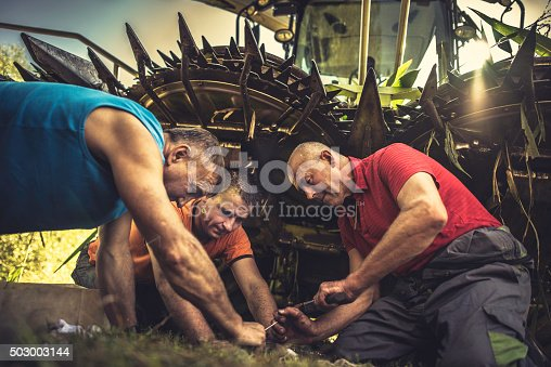Senior farmer repairing parts of a combine while two others are assisting him.