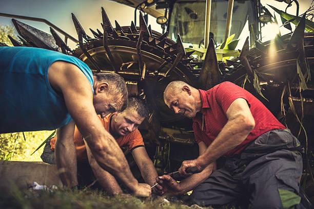 Three men kneeling by a combine harvester repairing it stock photo