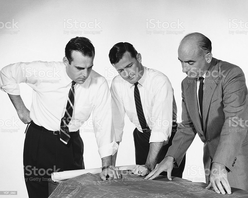Three men looking at blueprints royalty free stockfoto