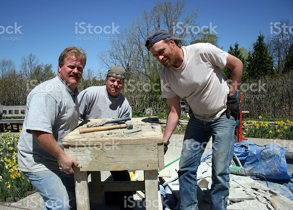 Three Men Moving Heavy Object royalty-free stock photo