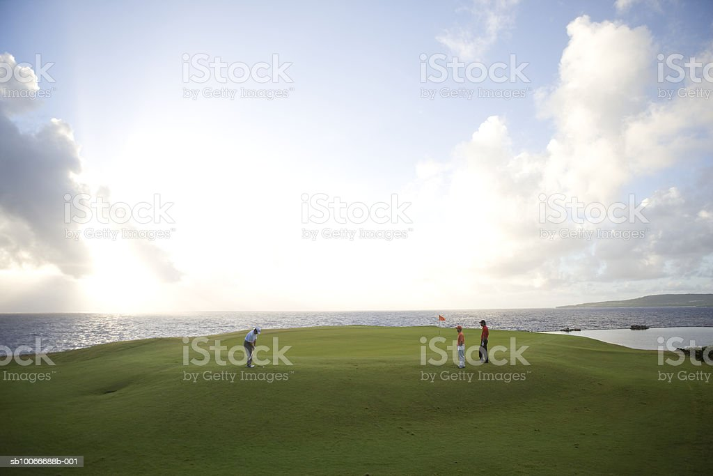 Three men on golf course, one putting and another two men watching royalty-free stock photo