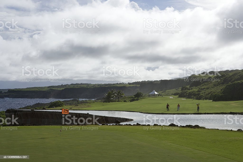 Three men on golf course playing golf royalty-free stock photo