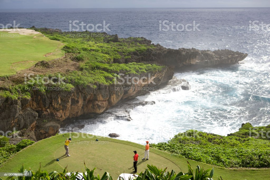 Three men playing golf by sea, elevated view royalty-free stock photo