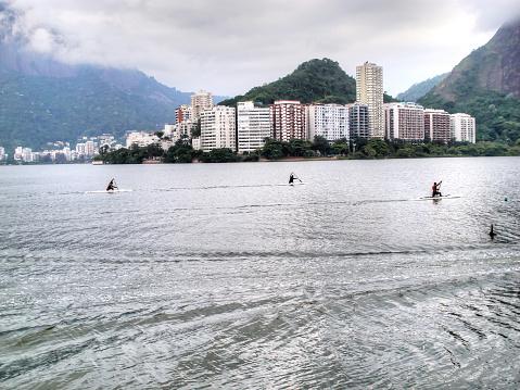 Three men racing on boards in Rio De Janeiro