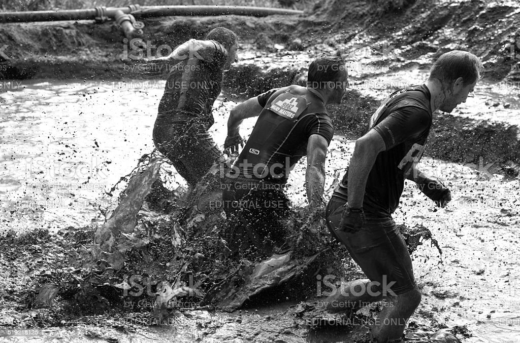 Three men running through a mud run obstacle stock photo