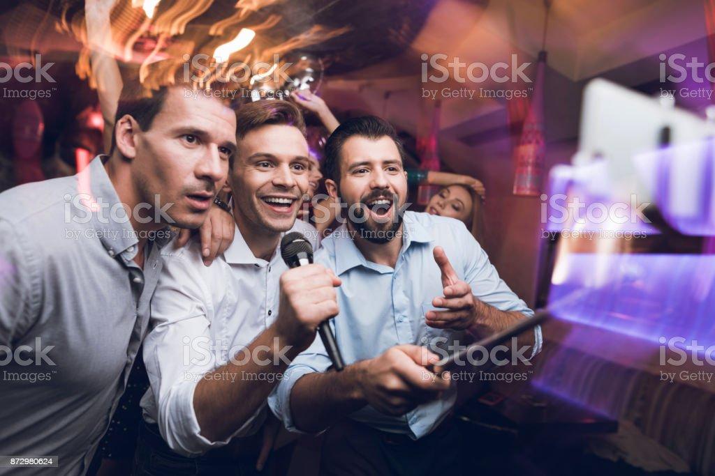 Drei Männer singen in einem Karaoke-Club. Jugendliche haben Spaß in einem Nachtclub. Sie sind sehr freundlich und Lächeln sie. – Foto