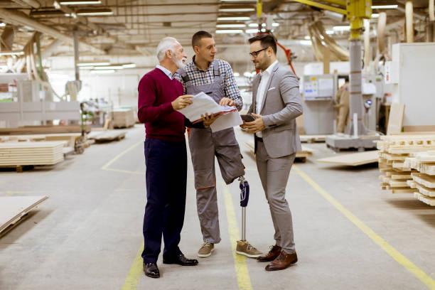 3 人立ち、家具工場で話し合う - disabilitycollection ストックフォトと画像