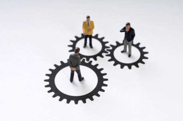 Three men standing in circles shaped liked gears stock photo