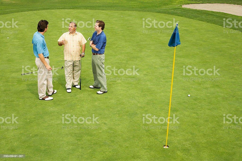 Three men standing on green royalty-free stock photo