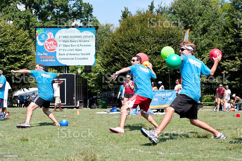 Three Men Throw In Unison At Outdoor Dodge Ball Game stock photo