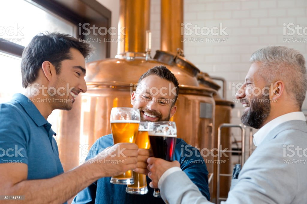 Three men toasting beers after work at micro brewery Three men toasting beers after work at micro brewery. Three man drinking beers and smiling at brewery. Adult Stock Photo