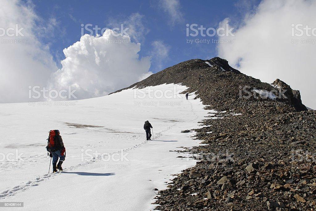 Three men trekking  on a mountain royalty-free stock photo