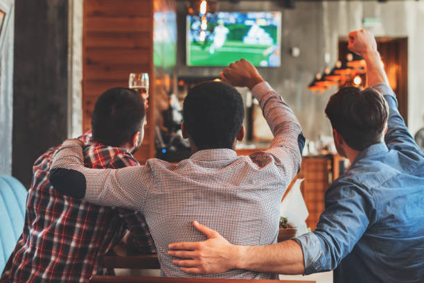 three men watching football on tv in bar - sport stock pictures, royalty-free photos & images