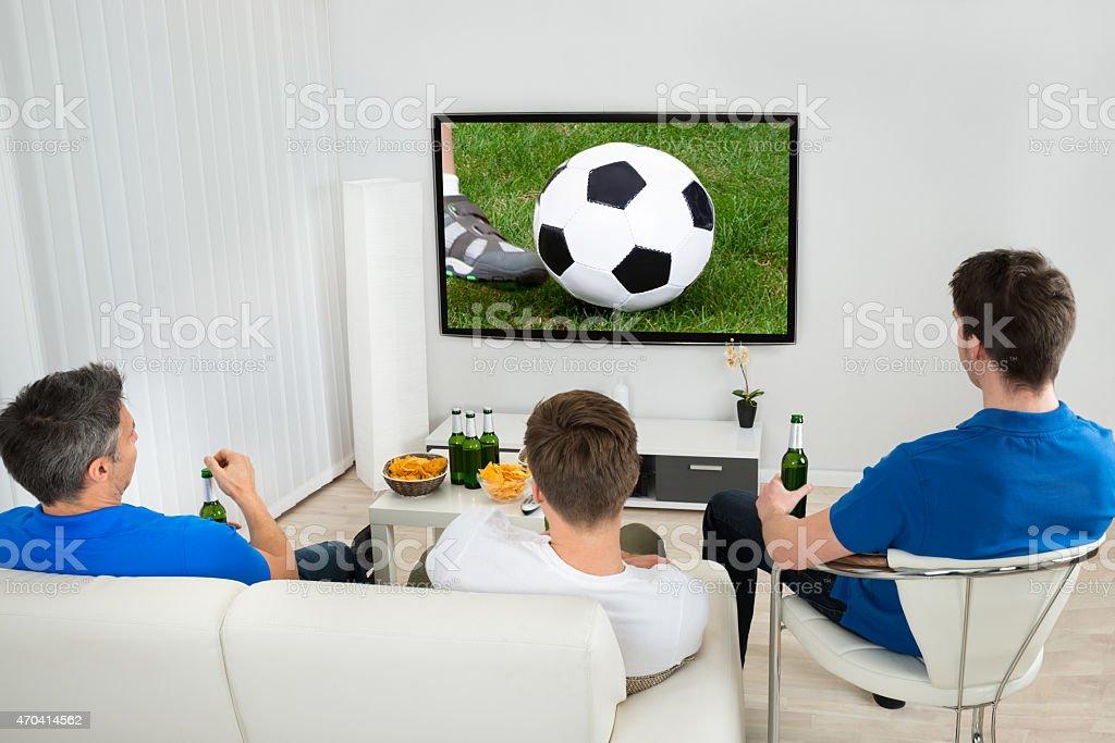 Tres hombres viendo el partido de fútbol - foto de stock