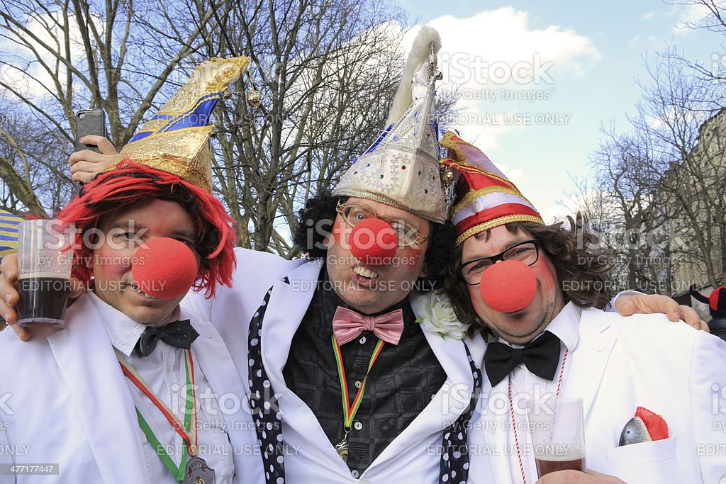 three men with clown noses in Dusseldorf street carnival stock photo