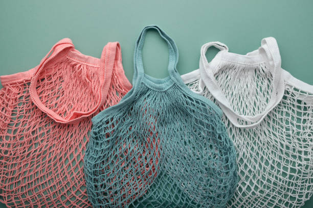 Three mesh bags of different colors on green background. Zero waste grocery shopping concept. stock photo