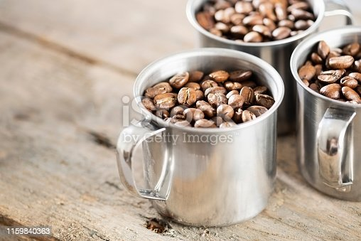 Three stainless steel cups full of dry roasted coffee beans. The cups have handles and are sitting on a wooden background.
