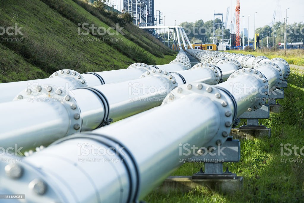 Three metal pipelines running parallel outside stock photo