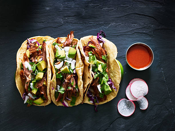 three mexican pork carnitas tacos flat lay composition - mexican food stock photos and pictures