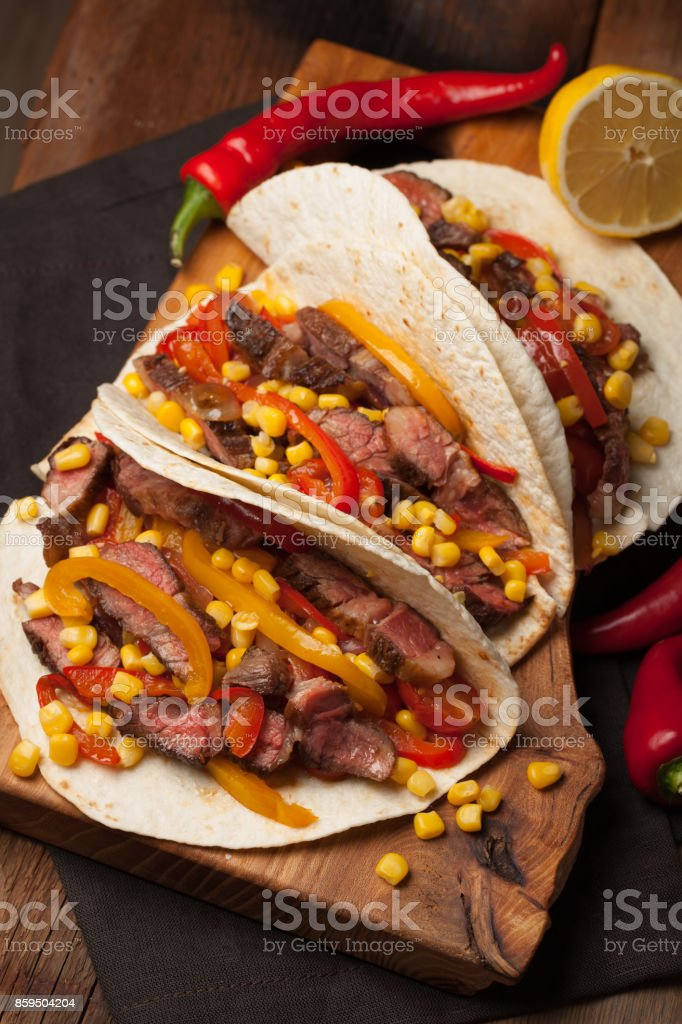 Three Mexican tacos with marbled beef, black Angus and vegetables on old rustic table. Mexican dish with sauces guacamole and salsa in bowls stock photo