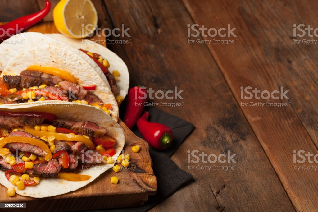 Three Mexican tacos with marbled beef, black Angus and vegetables on old rustic table. Mexican dish with sauces guacamole and salsa in bowls. copy space stock photo