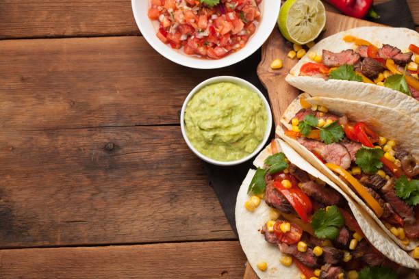 霜降り牛、ブラックアンガス古い素朴なテーブルの上の野菜と 3 つのメキシコのタコス。ソース ワカモレとサルサの鉢でメキシコ料理。コピー スペース平面図 - メキシコ料理 ストックフォトと画像