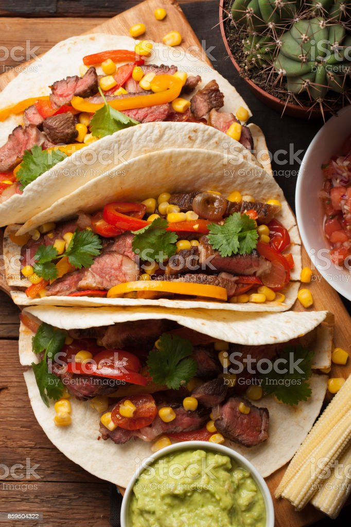 Three Mexican tacos with marbled beef, black Angus and vegetables on old rustic table. Mexican dish with sauces guacamole and salsa in bowls. top view stock photo
