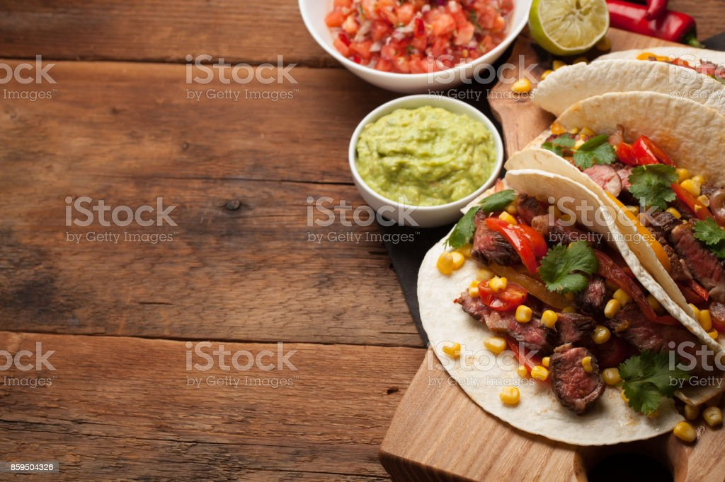 Three Mexican tacos with marbled beef, black Angus and vegetables on old rustic table. Mexican dish with sauces guacamole and salsa in bowls. Top view with copy space stock photo