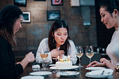レストランでケーキを祝う3人の半ば成人女性