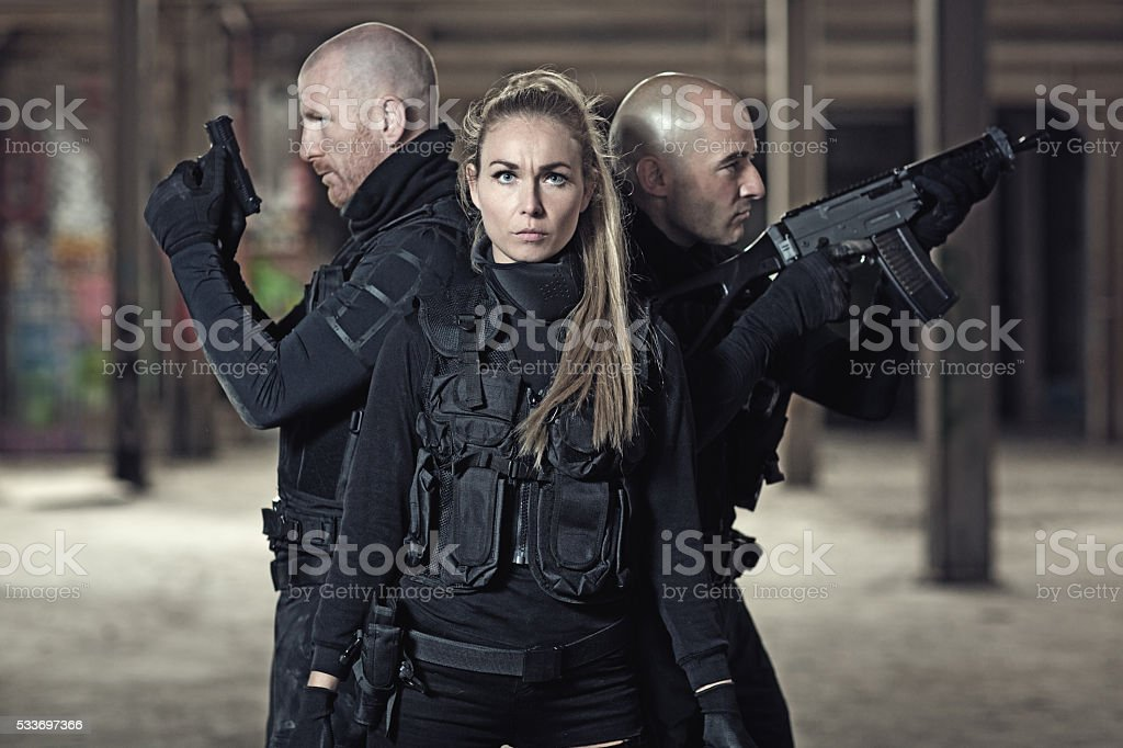 Three military swat team members holding weapons in abandoned warehouse stock photo