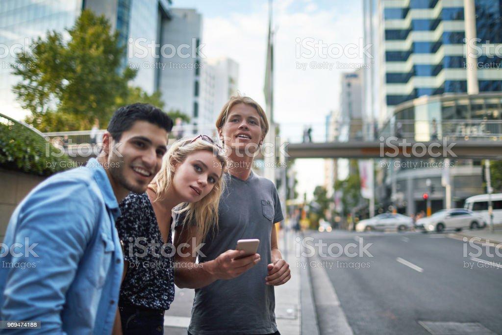 Três jovens amigos milenares esperando um táxi crowdsourced em Sydney - foto de acervo