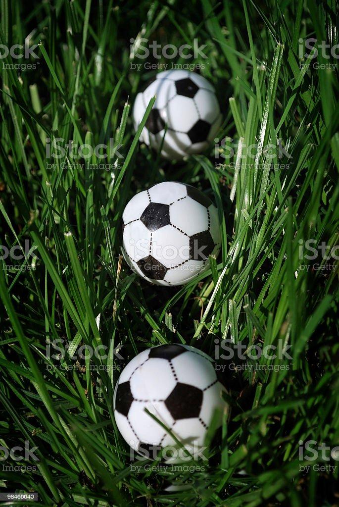 Miniatura tre palle calcio in erba alta foto stock royalty-free