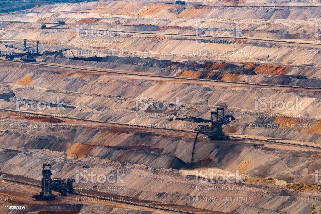 Drei Bergungsbagger in Braunkohlemine Hambach Blick auf braune, schwarz und orange erdige Terrassen. – Foto