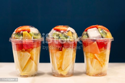 Three mixed fruit vitamin salad in the plastic glass ready to takeaway. Kiwi, pineapple, watermelon, coconut, strawberry, mango in plastic container. Copy space