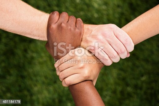 istock Three mixed hands linked in unity 451184179