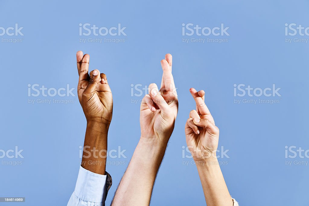 \'Three mixed hands are raised against a sky blue background, all with...