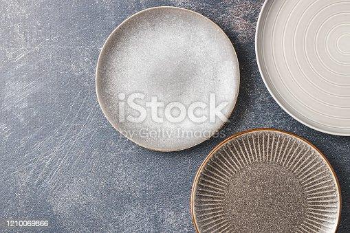 Three modern empty plates isolated on dark background