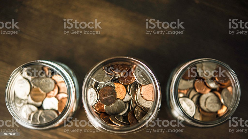 Three money jars filled with American currency stock photo