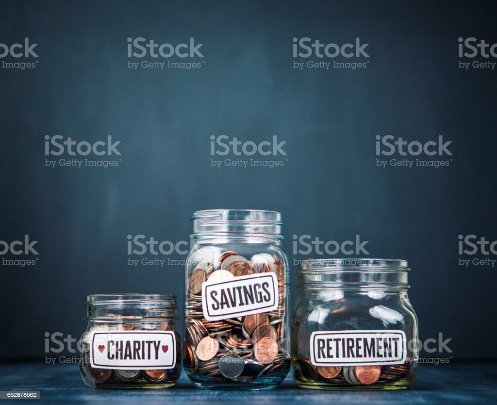Three money jars filled with American currency. Savings and donation concepts stock photo