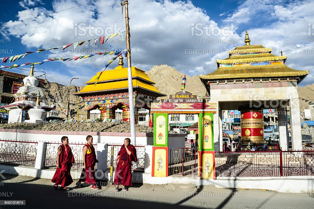 Three monks by a Buddhist praying compound stock photo